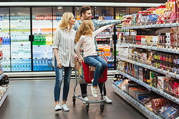 Cheery little girl sitting on a shopping cart and choosing candy with her parents at the supermarket